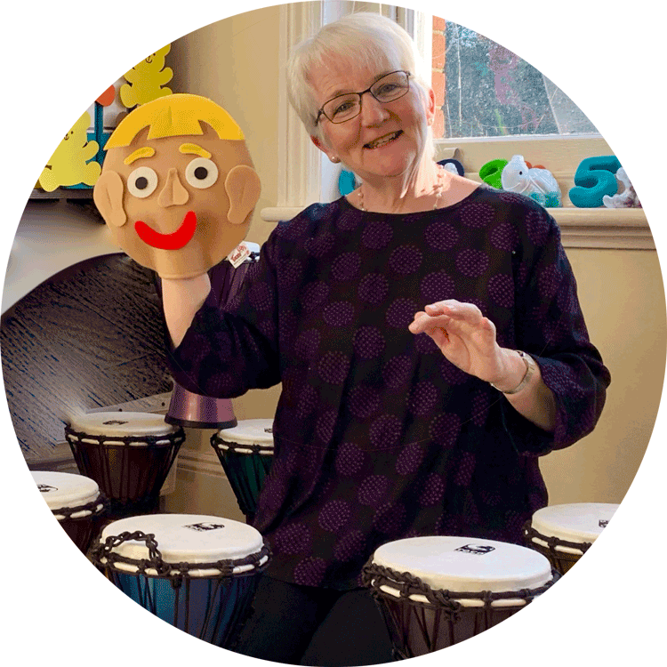 Dr Clare Seymour holding a hand puppet surrounded by bongos