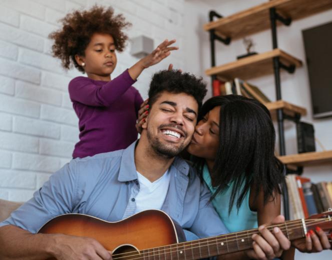 Family having fun playing guitar and singing at home.